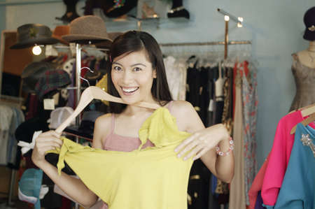 ebullient: Portrait of a young woman trying a blouse in a department store