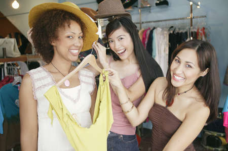 ebullient: Three young women trying a blouse in a department store LANG_EVOIMAGES