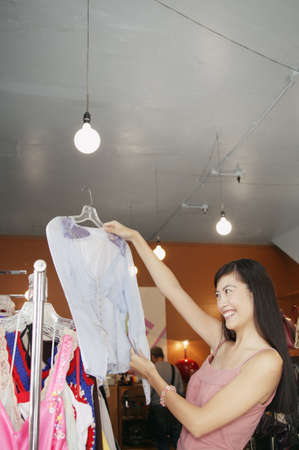ebullient: Young woman trying a blouse in department store LANG_EVOIMAGES