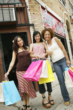 Low angle view of three young women holding shopping bags on the sidewalk Stock Photo - 16044467