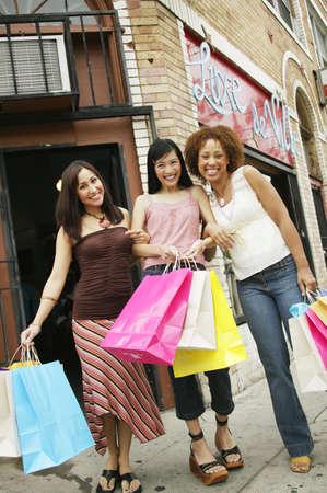 seres vivos: �ngulo de visi�n baja de tres mujeres j�venes con bolsas de compras en la acera