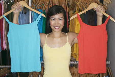 medium length: Woman holding two tank tops on hangers in her hands