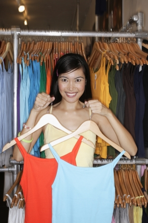 volition: Close-up of a young woman holding tank tops on hangers LANG_EVOIMAGES