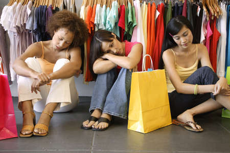 Three young women sitting on the floor in a department store Stock Photo - 16044480