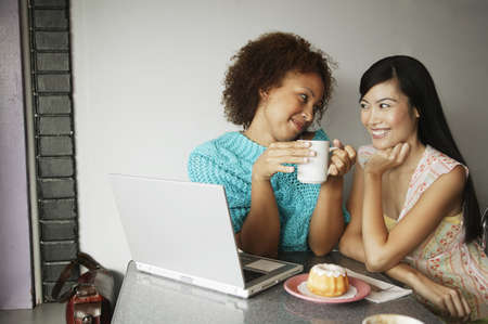 Close-up of two young women sitting with a laptop Stock Photo - 16044482