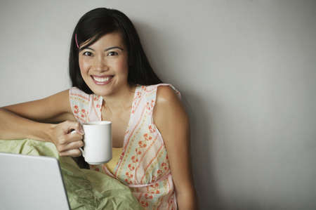 ebullient: Portrait of a young woman holding a coffee mug smiling