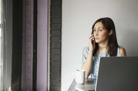 Young woman talking on a mobile phone Stock Photo - 16044486