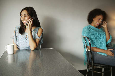Portrait of two young women talking on mobile phones Stock Photo - 16044490