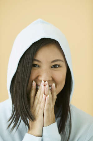 Teenage girl wearing a hooded jacket laughing with her hands on her mouth