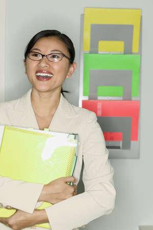 way of behaving: Teenage girl standing holding files smiling