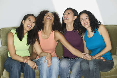 Group of young women sitting on a couch laughing