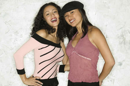 way of behaving: Two young women standing together looking at camera smiling