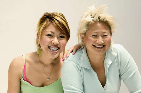 two persons only: Two young women looking at camera smiling
