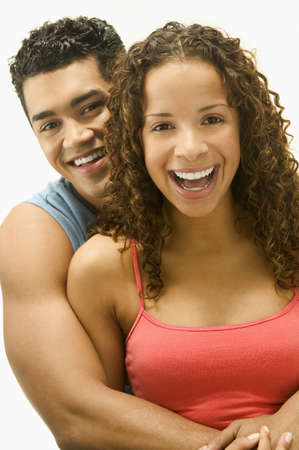 spanish ethnicity: Young couple holding each other looking at camera smiling LANG_EVOIMAGES
