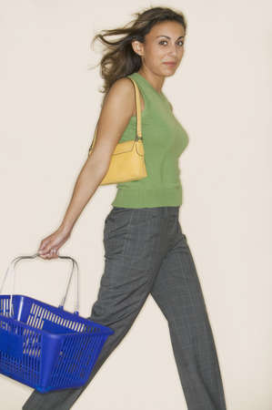 storage bin: Young woman walking holding a shopping basket looking at camera