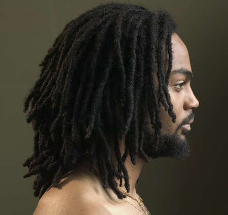 Side profile of a young man with dreadlocks