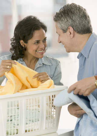 front end: Portrait of a couple folding clothes from a laundry basket