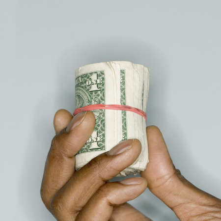 holding close: Human hand holding a roll of bank notes