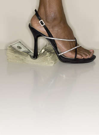 Woman foot in high heels standing on a stack of bank notes Stock Photo - 16044646