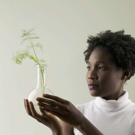 plantlet: Young woman holding a plant growing in a glass flask