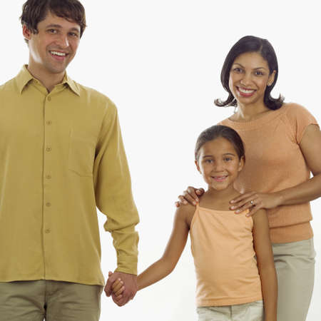 Portrait of a young couple and their daughter standing together looking at camera LANG_EVOIMAGES