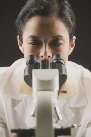 investigative: Female scientist looking through a microscope LANG_EVOIMAGES