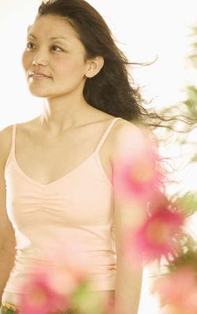 blase: Young woman behind flowers looking ahead