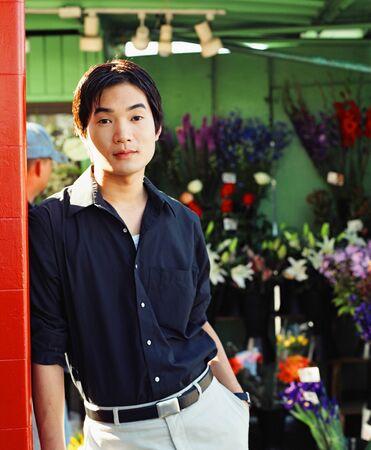 young man standing: Ritratto di un giovane uomo in piedi in un negozio di fiori