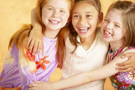 Three young girls holding each other smiling LANG_EVOIMAGES
