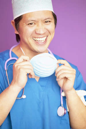 way of behaving: Portrait of a male doctor wearing full scrubs smiling