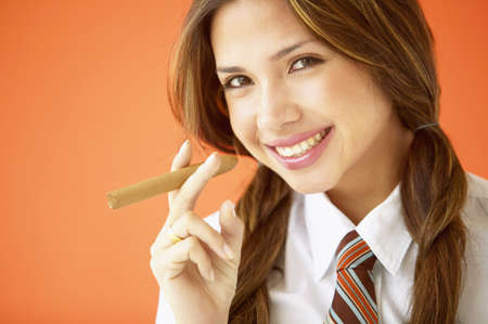 unknown age: Portrait of a young woman smiling holding a cigar
