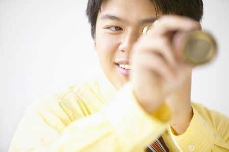 Businessman looking through a telescope smiling Stock Photo - 16044750