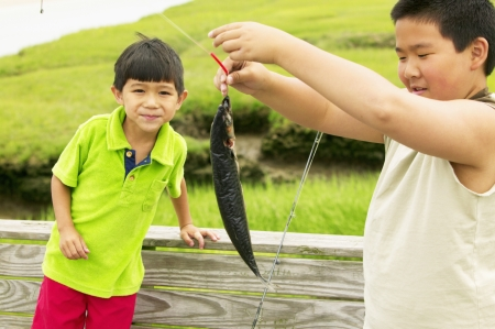 fish rearing: Two young boys holding a fish