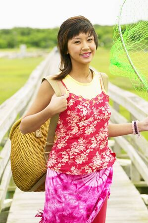 Young woman holding a basket and a fishing net Stock Photo - 16044757