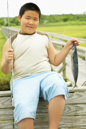 rearing of fish: Young boy sitting holding a fishing rod and a fish