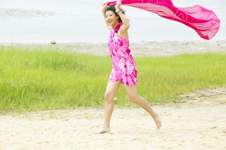 cape cod style: Young woman holding a sarong over her head running LANG_EVOIMAGES