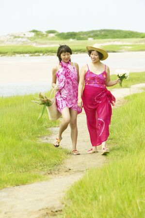 Two women walking on a path holding flowers Stock Photo - 16044769