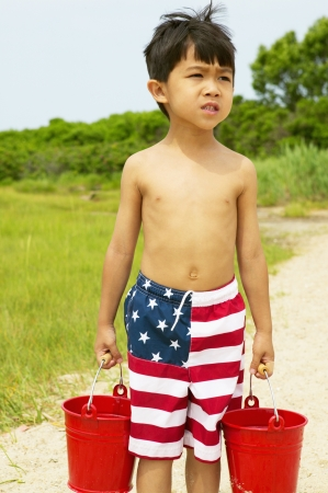 informant: Young boy carrying two buckets at the beach LANG_EVOIMAGES