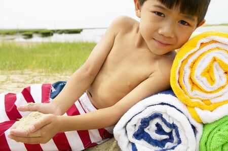 informant: Young boy sitting on the beach leaning against towels LANG_EVOIMAGES