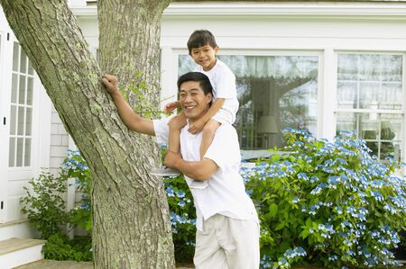 Mature man standing with a young boy sitting on his shoulders