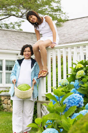 Portrait of a mid adult woman standing and a young woman sitting on a fence in a garden Stock Photo - 16044782