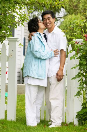 anecdote: Woman kissing a man standing together on a lawn LANG_EVOIMAGES