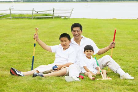 Man with two young boys sitting on a lawn LANG_EVOIMAGES