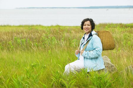 Mid adult woman sitting in tall grass holding a basket Stock Photo - 16044786