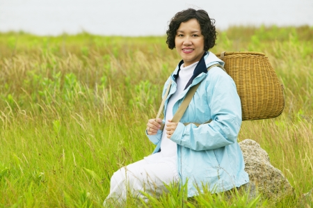 informant: Mid adult woman sitting in tall grass holding a basket