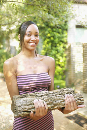 ebullient: Young woman holding a piece of wood