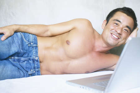 restfulness: Mid adult man lying on a bed operating a laptop