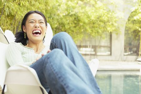 Young woman sitting on a chair outdoors laughing Stock Photo