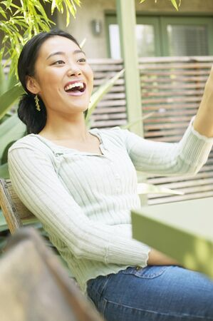 Young woman sitting on a chair outdoors smiling Stock Photo - 16044868