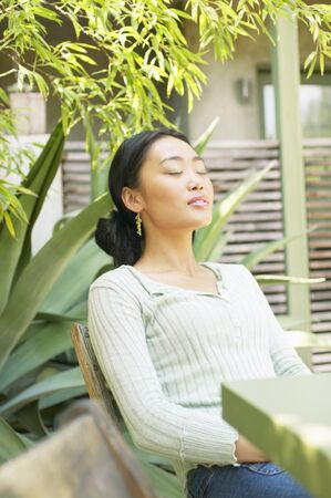 ebullient: Young woman sitting on a chair outdoors with her eyes closed